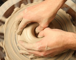 Closeup of hands working on pottery wheel